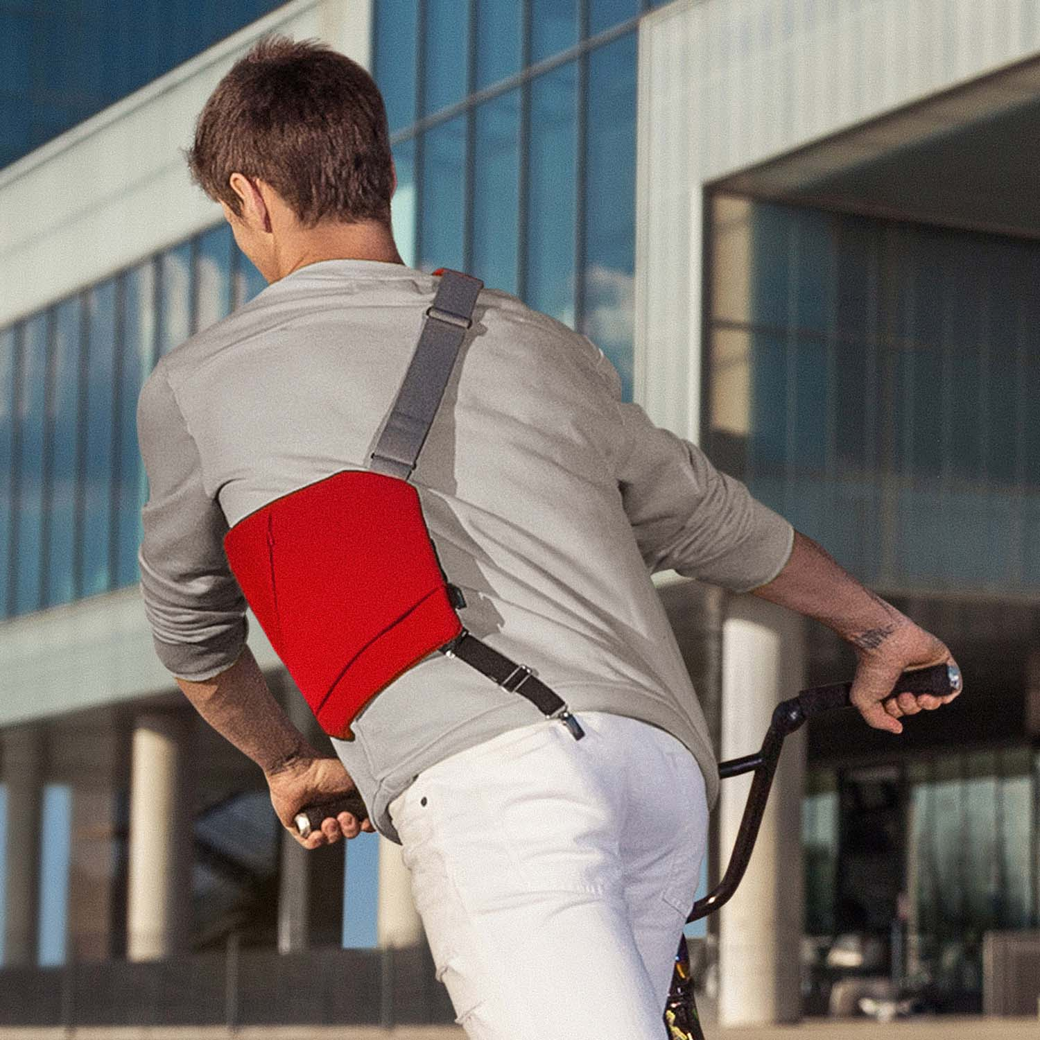Man on bike doing stunts with a red textile shoulder crossbody bag by Baggizmo