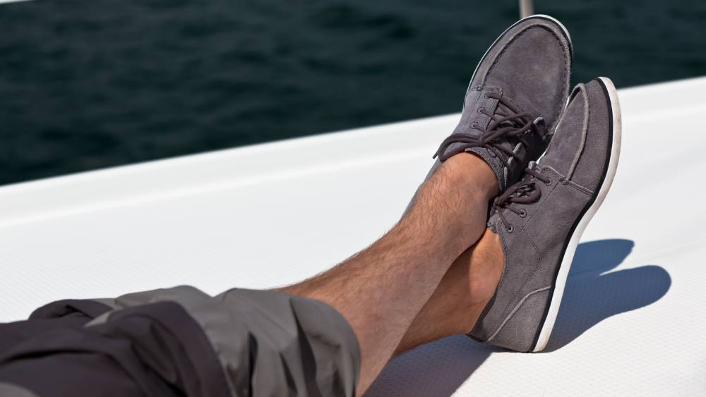 Man wearing grey boat shoes on a boat