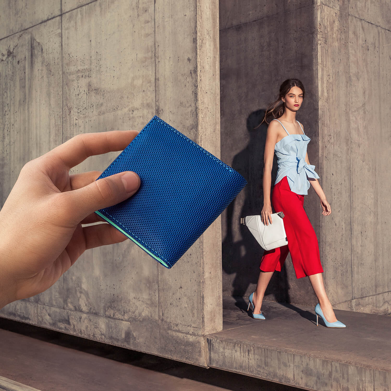 Hand holding a blue smart wallet and woman in red pants walking