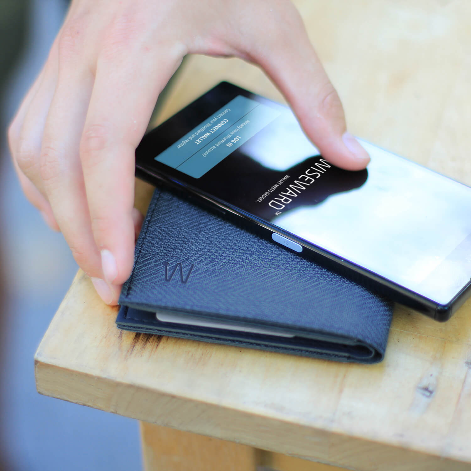 Hand touching a smart wallet and smartphone
