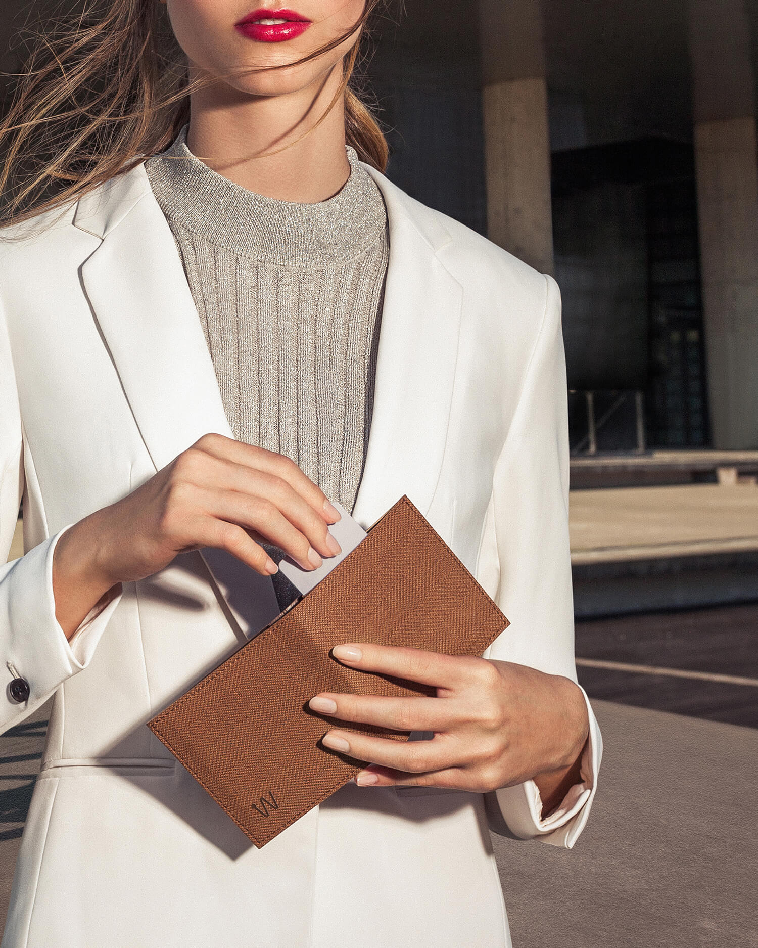 Woman in white suit holding a brown smart wallet