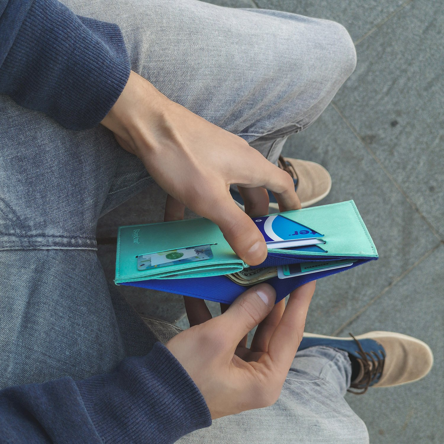 Man holding blue smart wallet with credit cards and cash