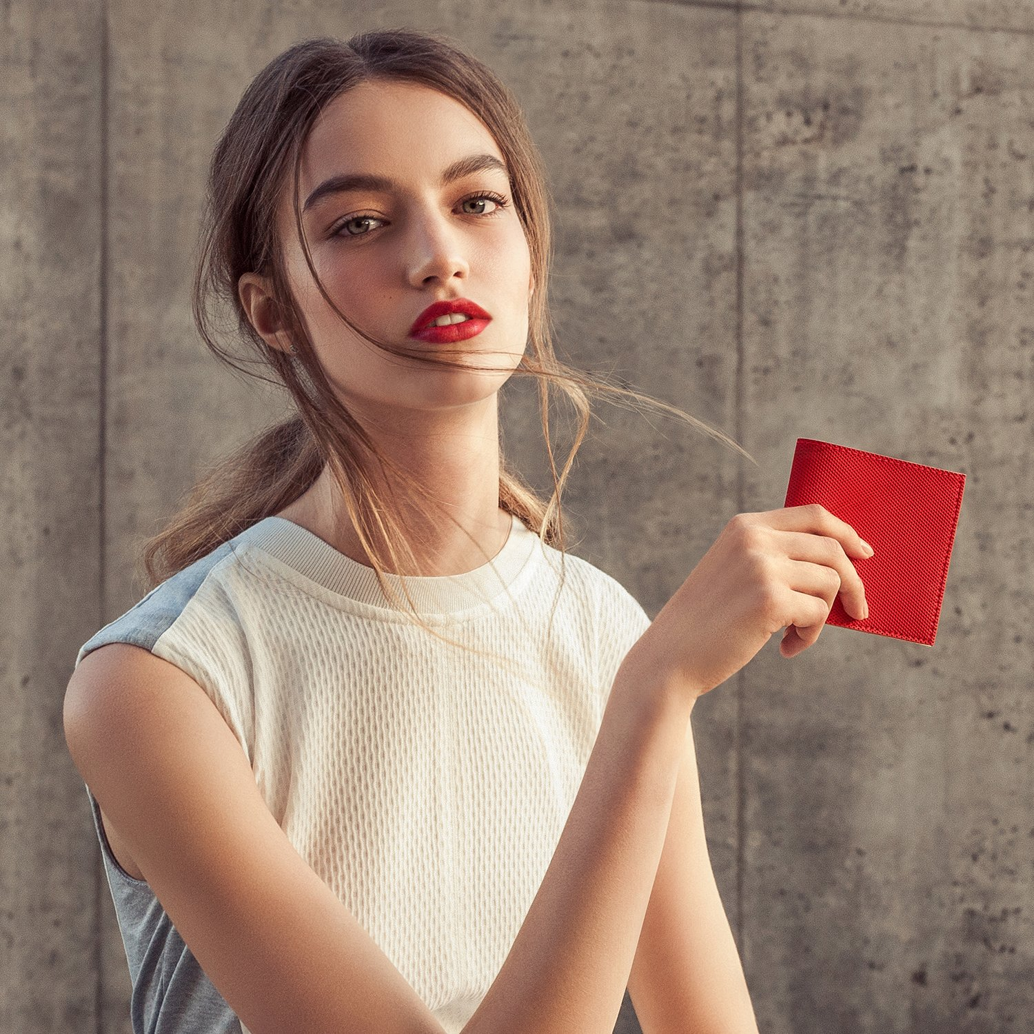 Woman with red lipstick holding a red smart Baggizmo Wiseward wallet