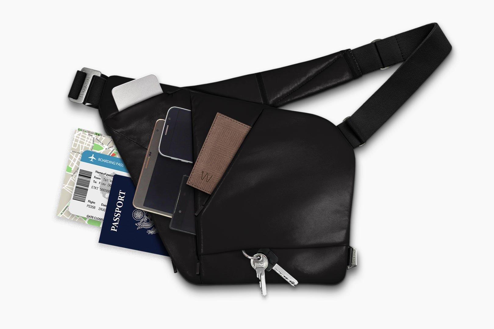 Black leather crossbody bag full of things, gadgets, passport, keys