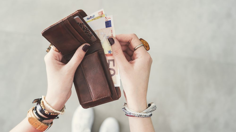 Woman with bracelets holding a bifold wallet with euros