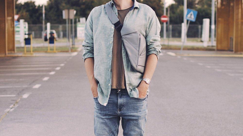 Man in a shirt wearing a grey leather crossbody bag