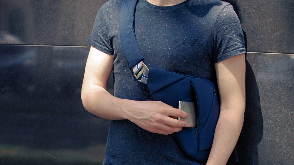 Man in blue T shirt wearing a blue textile crossbody bag with NFC tag