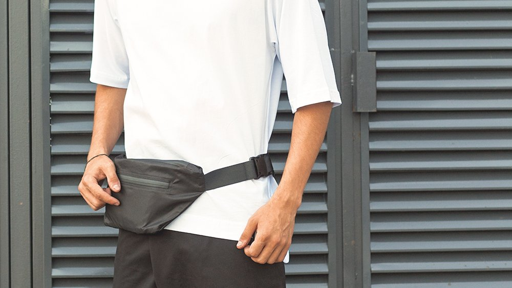 Man in white T-shirt carrying a fanny pack