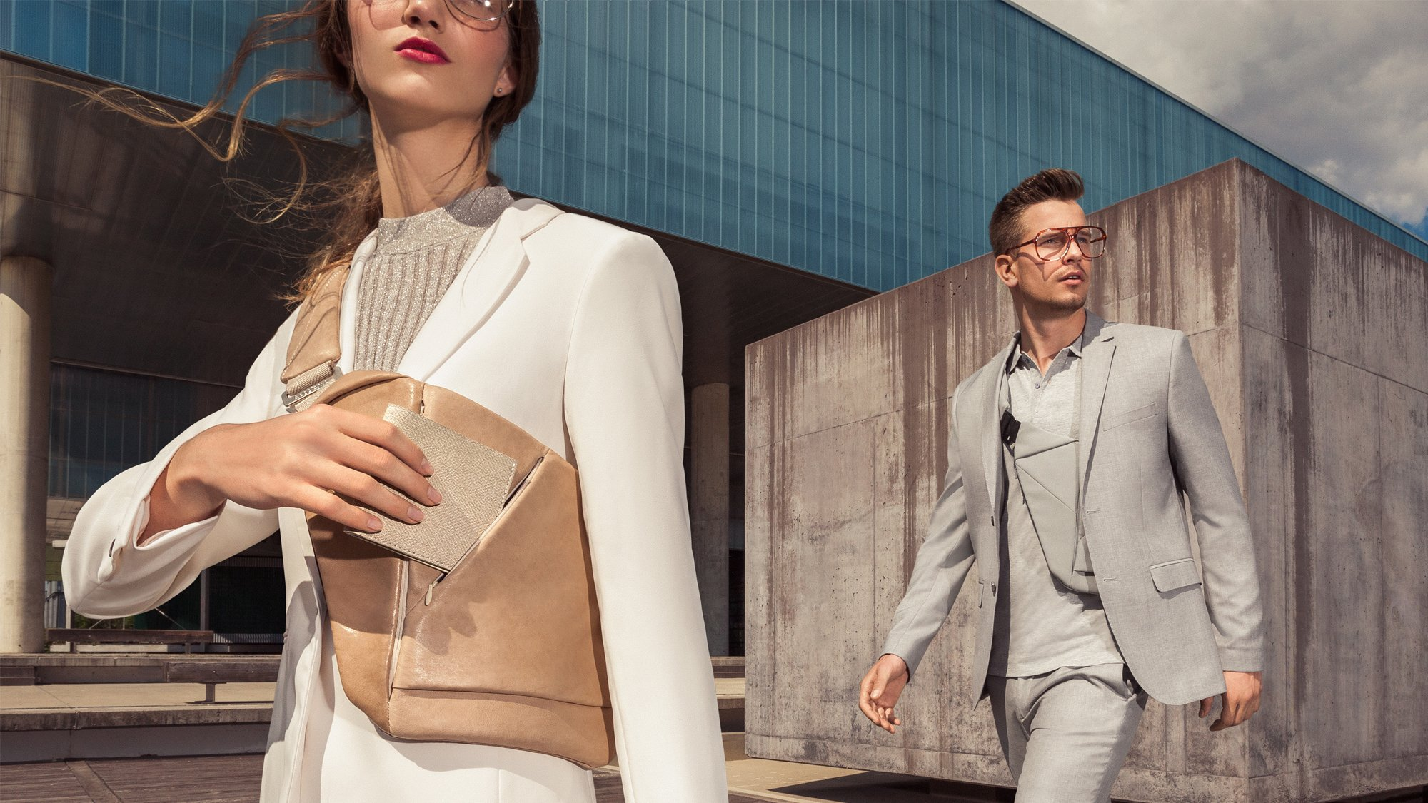 Woman in white suit and man in grey suit wearing Baggizmo genuine leather crossbody bag