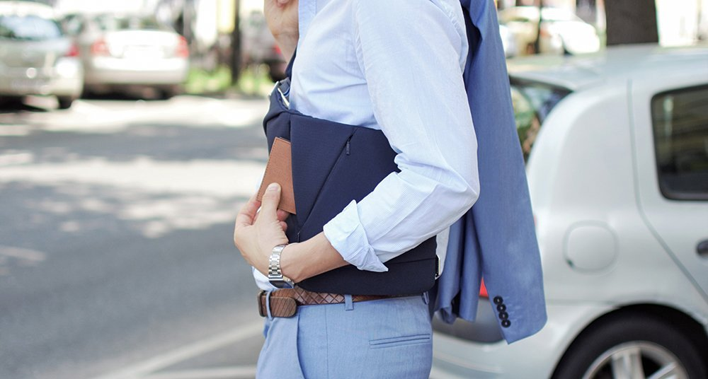 Man wearing a crossbody bag and holding a smart wallet