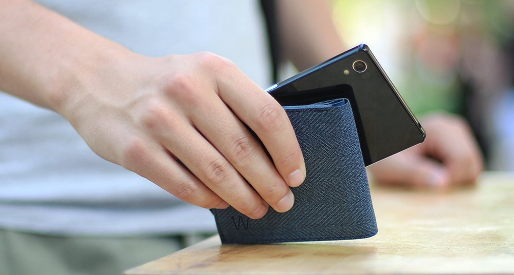Man holding a smart wallet and a phone in his hand