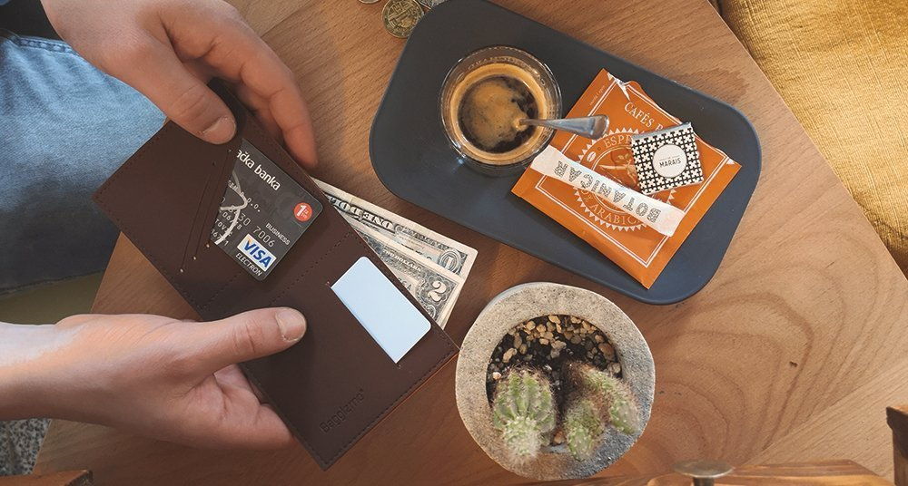 Man holding an RFID wallet with dollars and coffee on the table