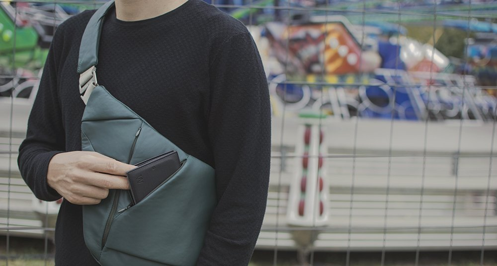 Man in a sweater wearing leather green crossbody bag and holding a slim wallet