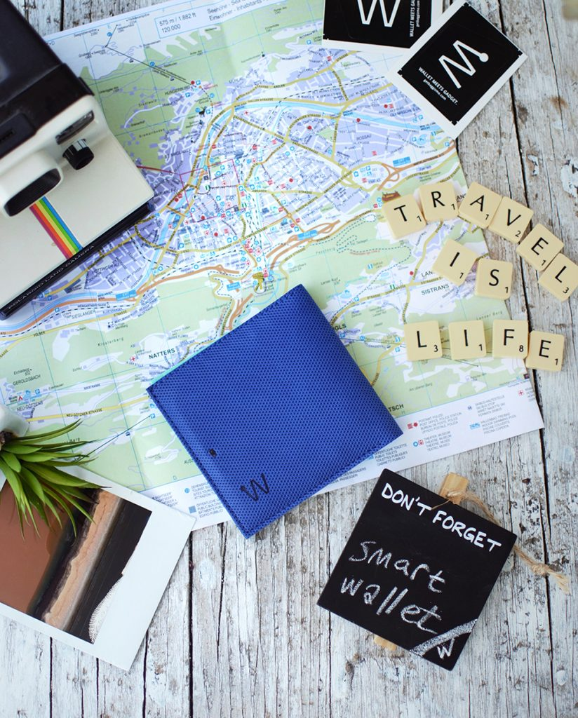 Blue smart wallet on the table with a map and polaroid