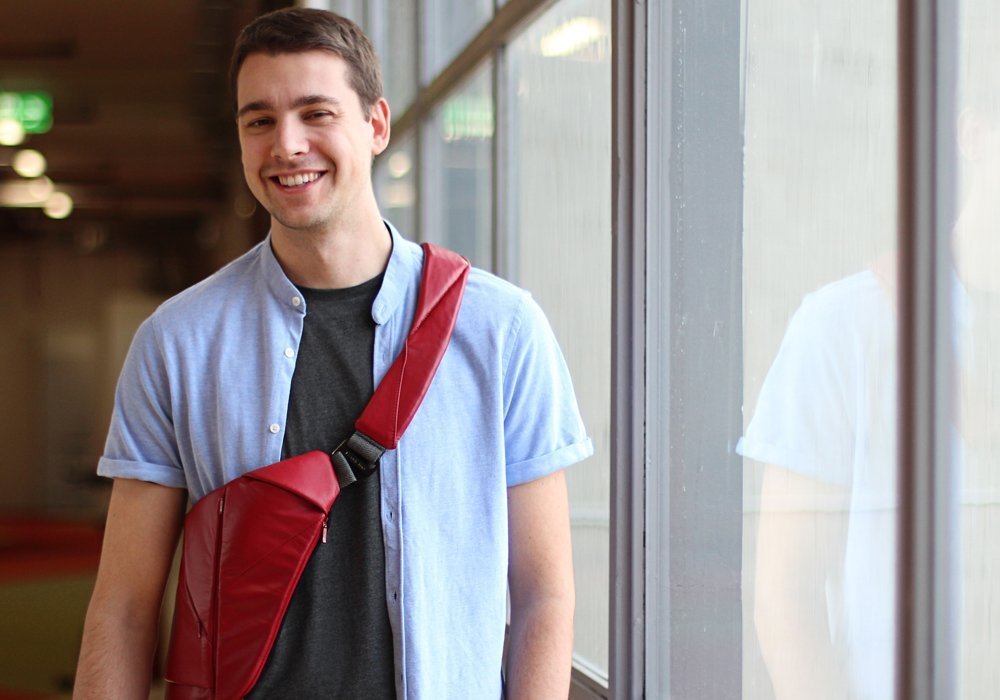 man wearing red leather crossbody bag