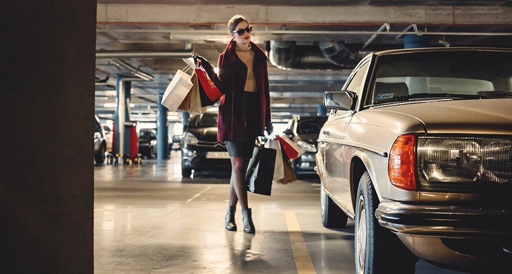 Woman shopping and walking next to a car