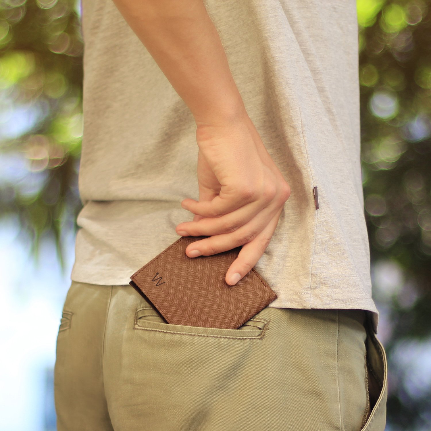 Man putting tweed smart wallet into the pocket of his pants